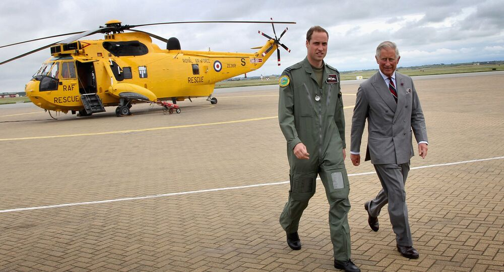 Britain's Prince Charles (R) and his son Prince William walk back to the RAF Rescue base after Prince William showed his father round his RAF Rescue helicopter at RAF Valley on July 9, 2012, in north-west England
