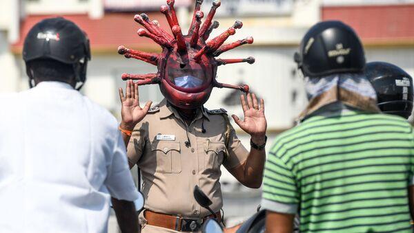 Un poliziotto indiano indossa un casco a tema coronavirus - Sputnik Italia