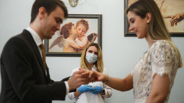 Mosca. Una coppia si scambia gli anelli durante un matrimonio. Proseguono le cerimonie con le regole per la pandemia coronavirus - Sputnik Italia
