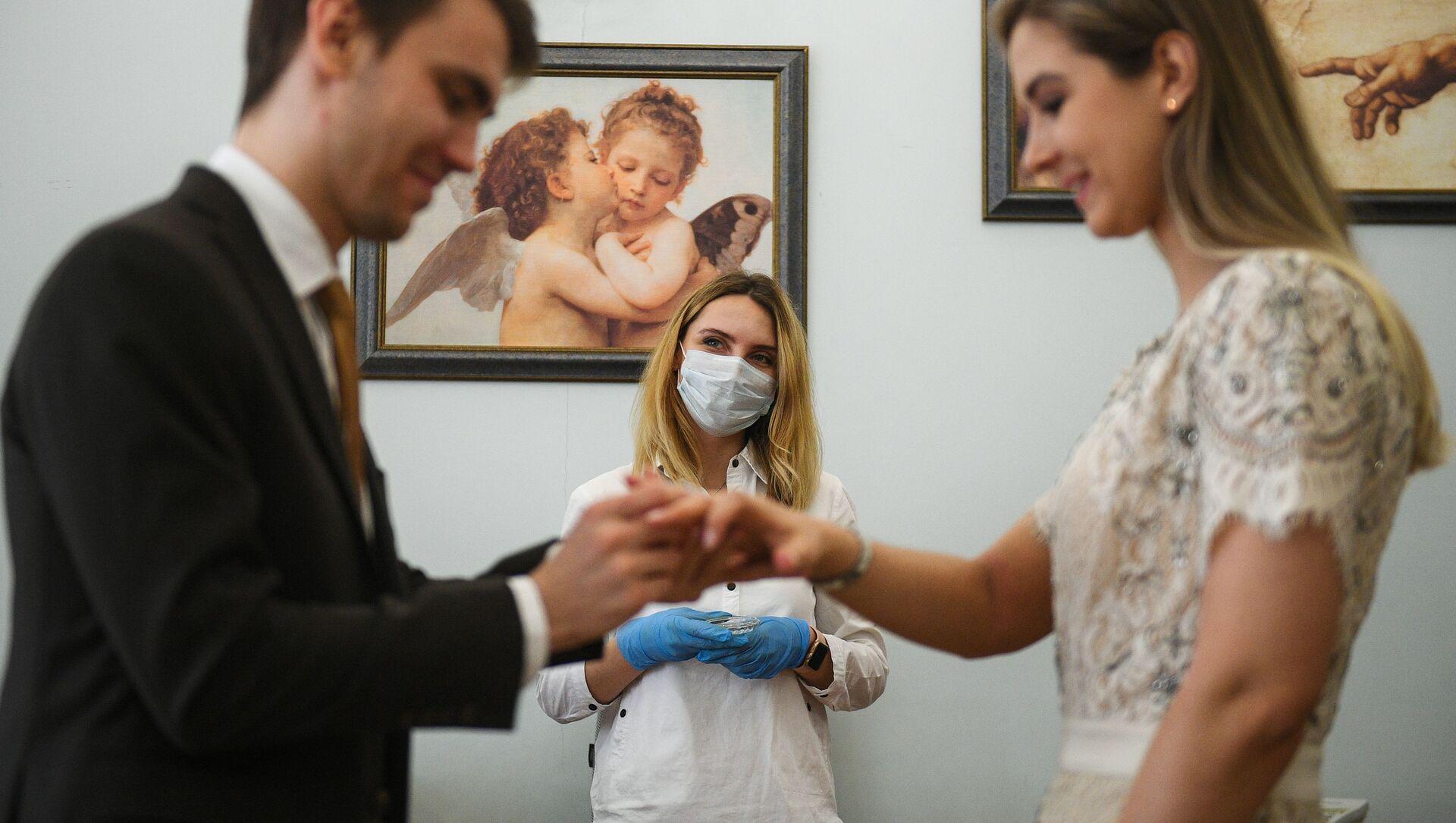 Mosca. Una coppia si scambia gli anelli durante un matrimonio. Proseguono le cerimonie con le regole per la pandemia coronavirus - Sputnik Italia, 1920, 28.04.2021