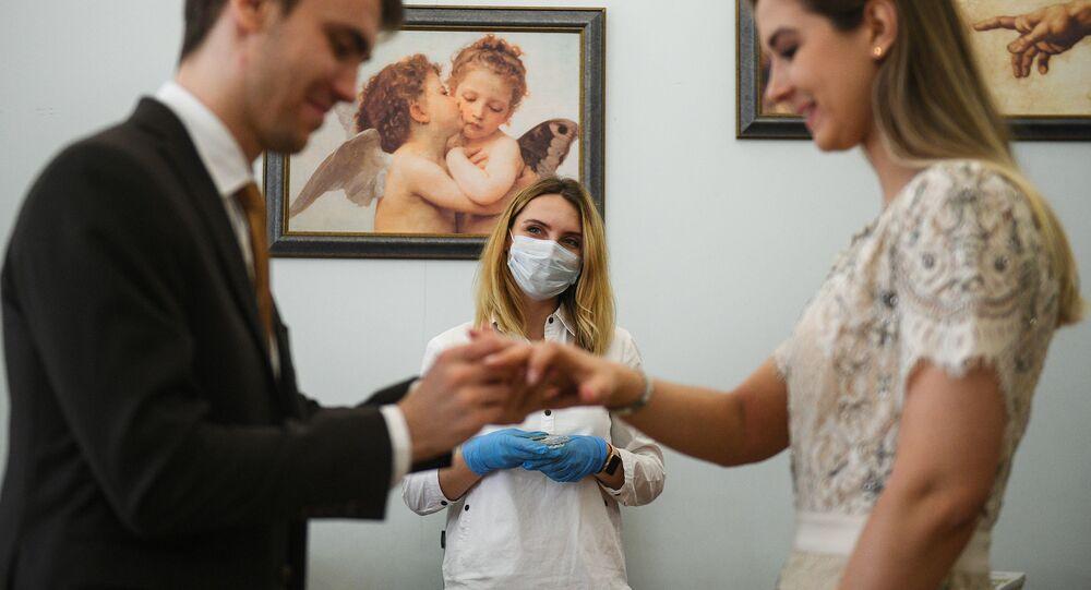 Mosca. Una coppia si scambia gli anelli durante un matrimonio. Proseguono le cerimonie con le regole per la pandemia coronavirus