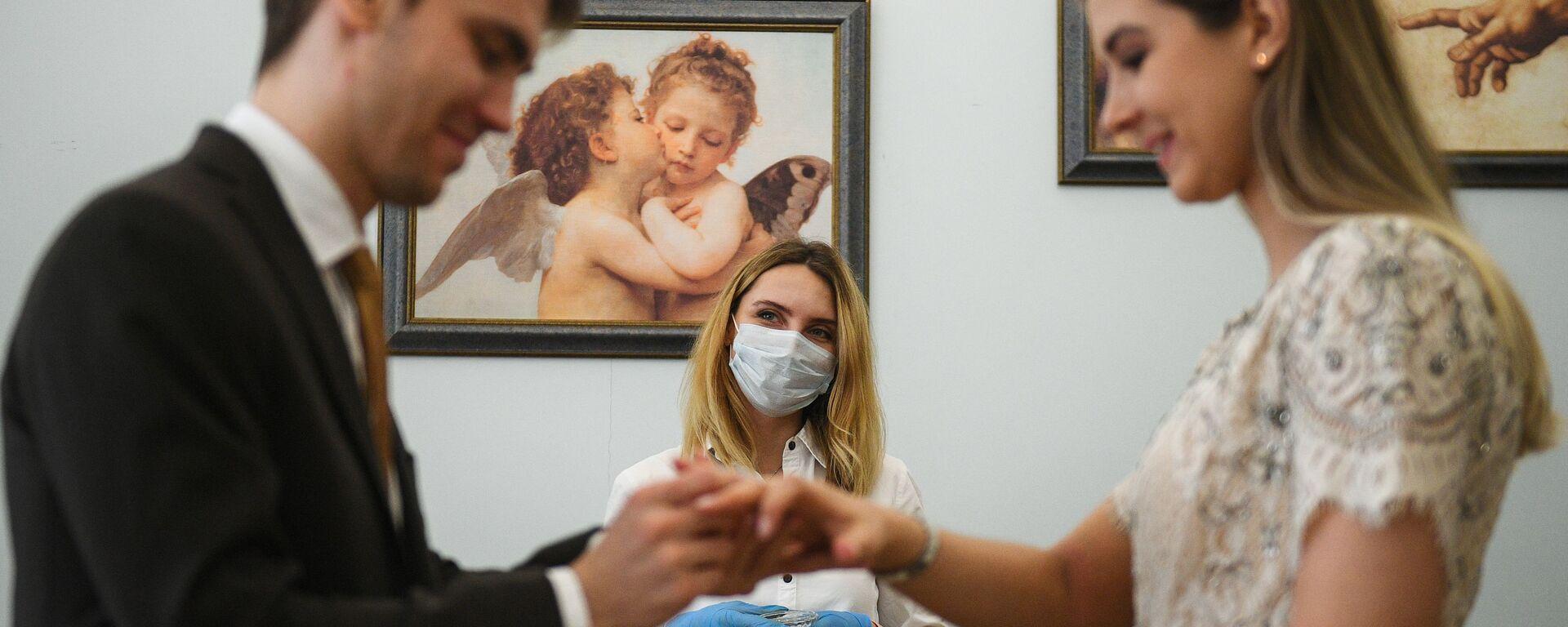 Mosca. Una coppia si scambia gli anelli durante un matrimonio. Proseguono le cerimonie con le regole per la pandemia coronavirus - Sputnik Italia, 1920, 02.08.2021