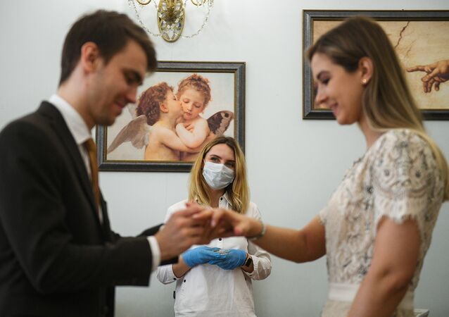 A couple exchanges rings during a wedding ceremony in Moscow. Weddings without guests (as well as divorce procedures) continue in the city amid the coronavirus pandemic.