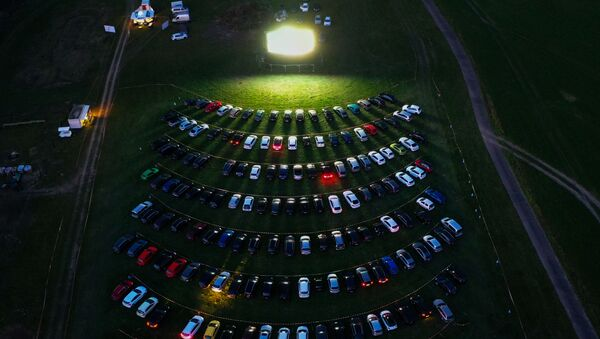 An aerial view shows cinema goers sitting in their cars parked at a drive-in cinema in Marl, western Germany, on April 6, 2020, one of the few entertainments still allowed due to the spread of the novel coronavirus COVID-19.  - Sputnik Italia