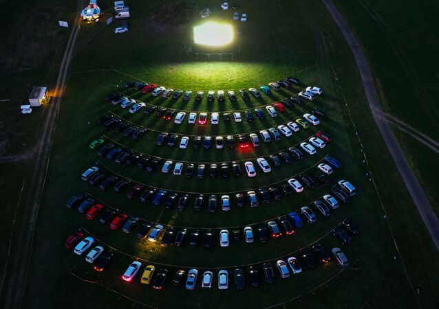 An aerial view shows cinema goers sitting in their cars parked at a drive-in cinema in Marl, western Germany, on April 6, 2020, one of the few entertainments still allowed due to the spread of the novel coronavirus COVID-19.