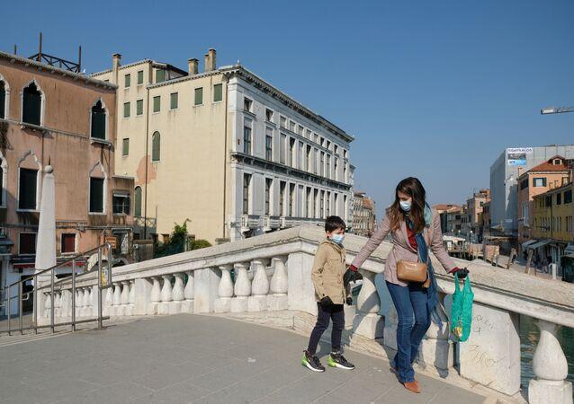 Una donna con il suo figlio in mascherine a Venezia