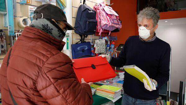 Un venditore e un cliente in mascherine in un negozio a Catania - Sputnik Italia