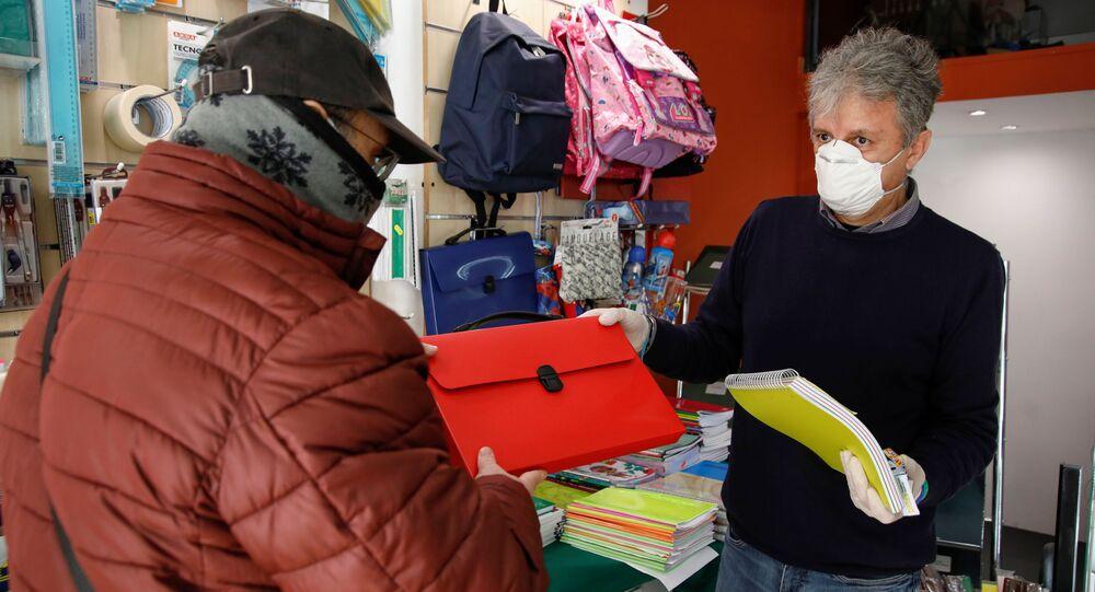 Un venditore e un cliente in mascherine in un negozio a Catania