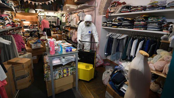Un dipendente in costume protettivo in un negozio per bambini a Roma - Sputnik Italia