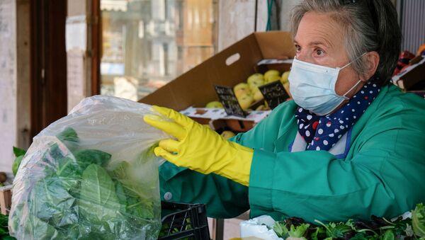 Una signora in mascherina vende prodotti alimentari a Venezia - Sputnik Italia