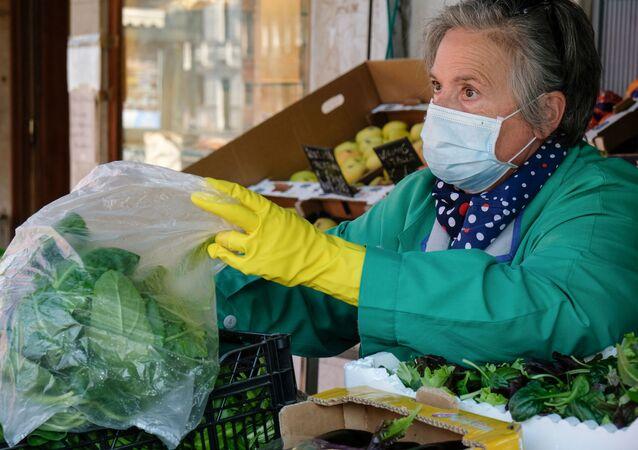 Una signora in mascherina vende prodotti alimentari a Venezia