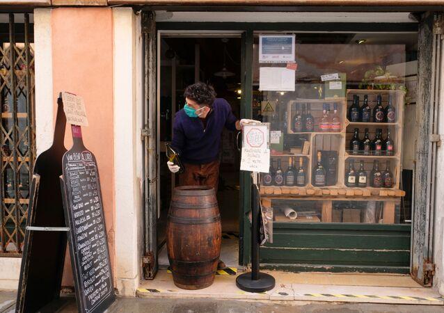 Un venditore in guanti e mascherina in un negozio a Venezia