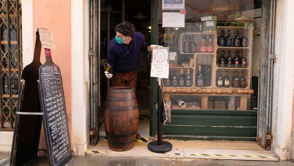 Un venditore in guanti e mascherina in un negozio a Venezia - Sputnik Italia