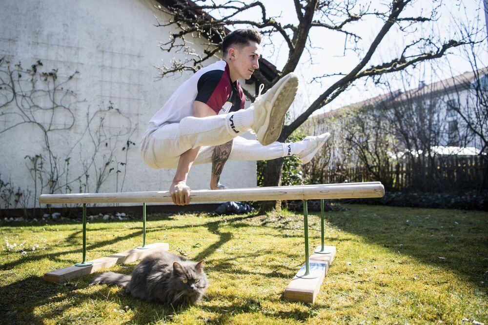 Marcel Nguyen, ginnasta, si allena nel giardino mentre il gatto di famiglia Coco siede sul prato, Germania, il 25 marzo 2020