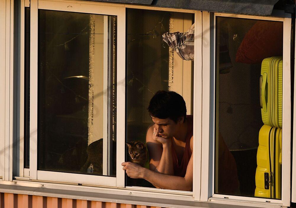 Un ragazzo con un gatto sul balcone di un condominio a Mosca