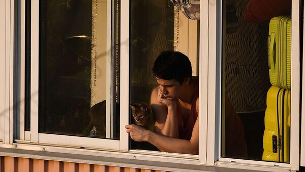 Молодой человек с кошкой на балконе многоквартирного дома в Москве - Sputnik Italia