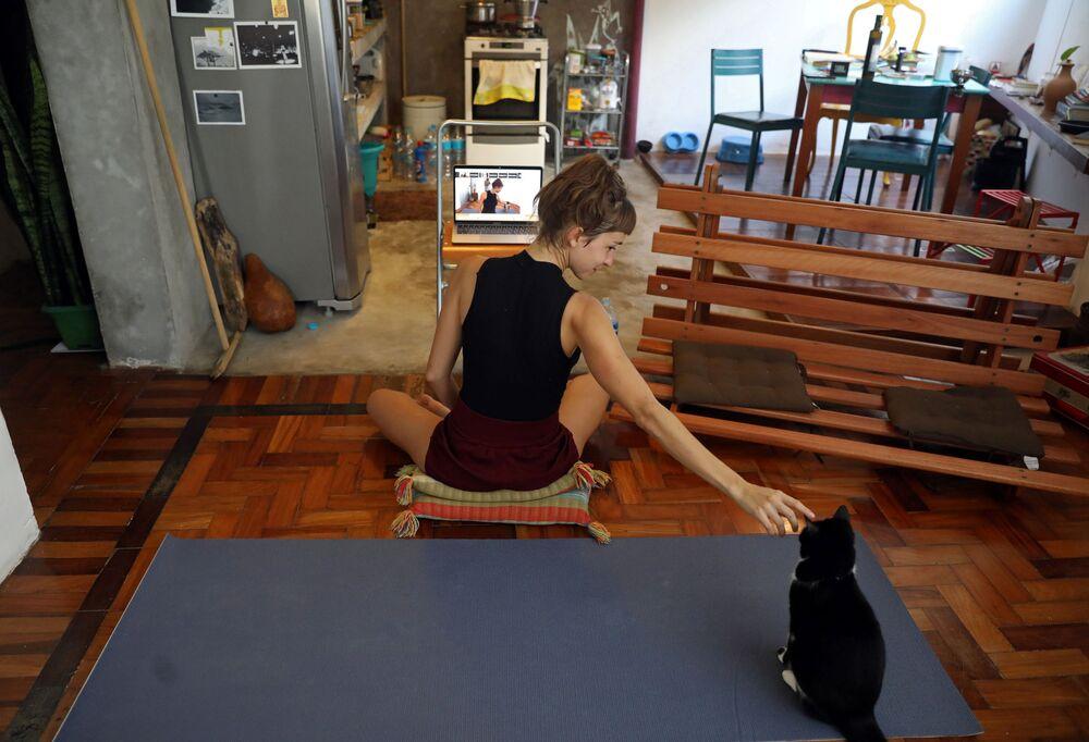 L'istruttrice di yoga Chris Igreja accarezza il suo gatto durante una lezione di yoga online a Rio de Janeiro, Brasile, il 19 marzo 2020