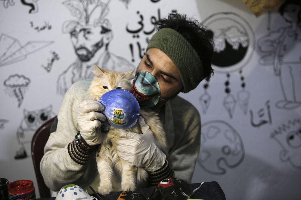 L'artista palestinese Dorgham Krakeh tiene davanti a un gatto una maschera protettiva dipinta a Gaza, il 24 marzo 2020