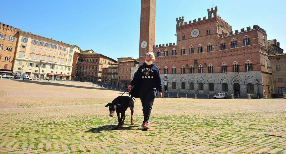 Una donna porta a spasso un cane sulla Piazza del Campo a Siena