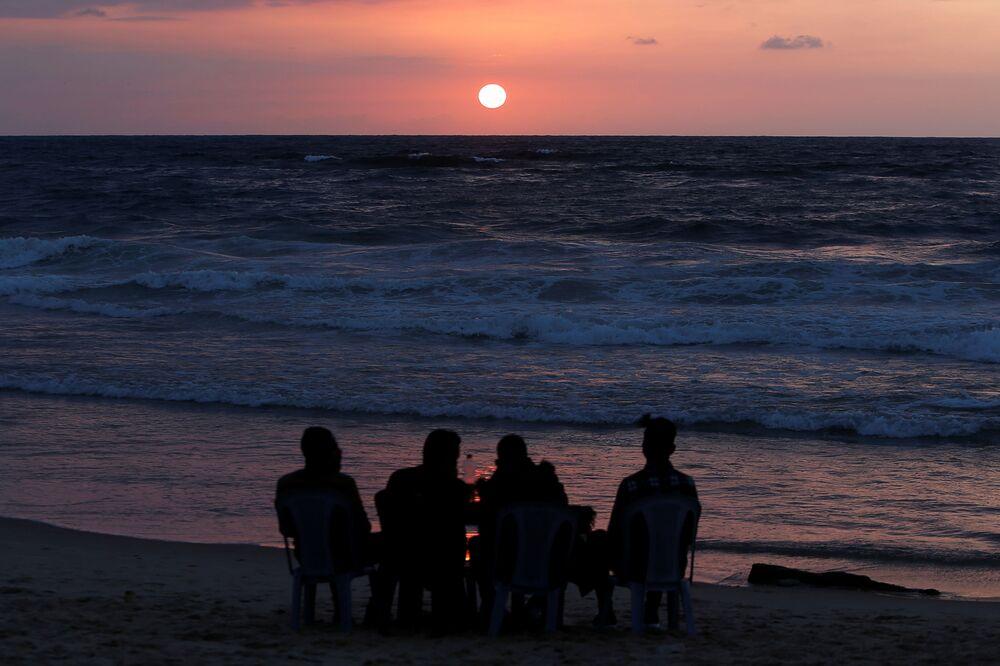 I palestinesi si godono il tramonto su una spiaggia nella Striscia di Gaza, il 10 aprile 2020