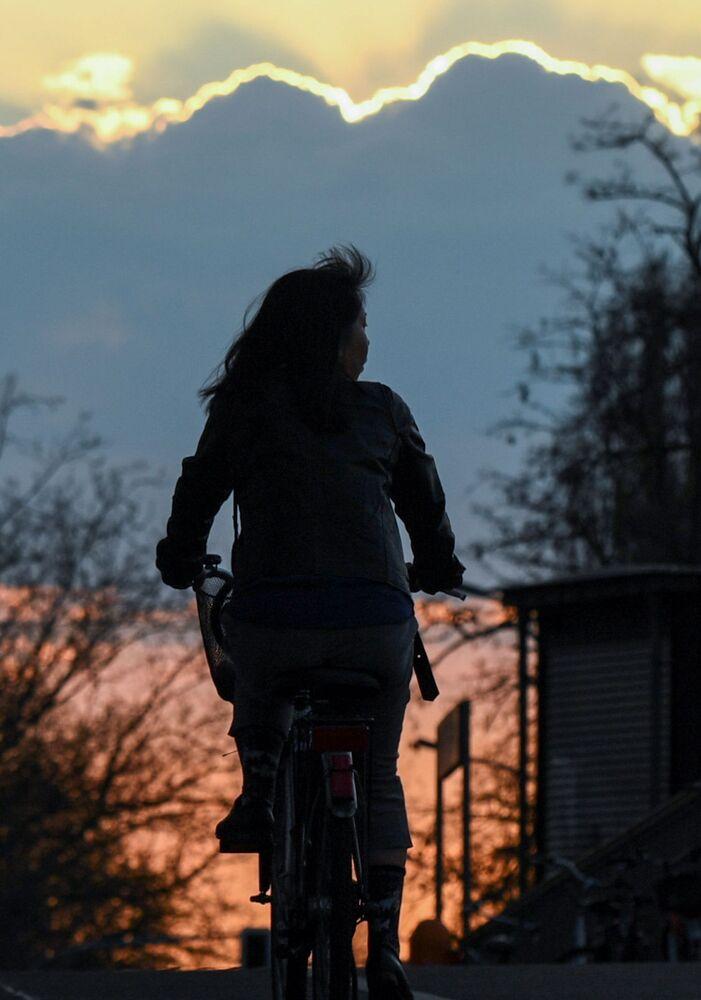 Una donna in bici al tramonto a Berlino, Germania, il 12 aprile 2020