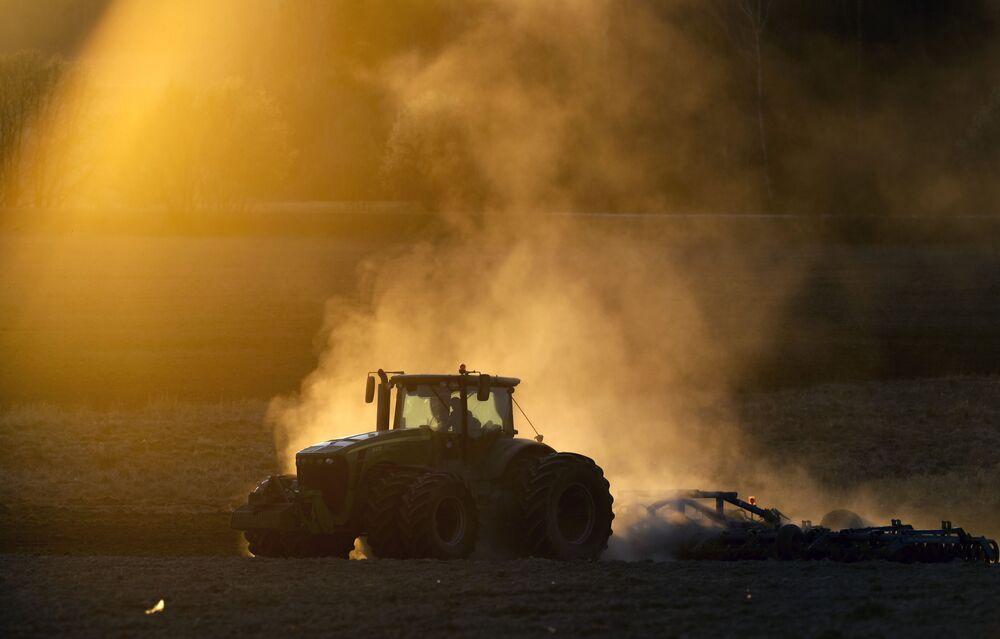 Un trattore in un campo al tramonto a Minsk, Bielorussia