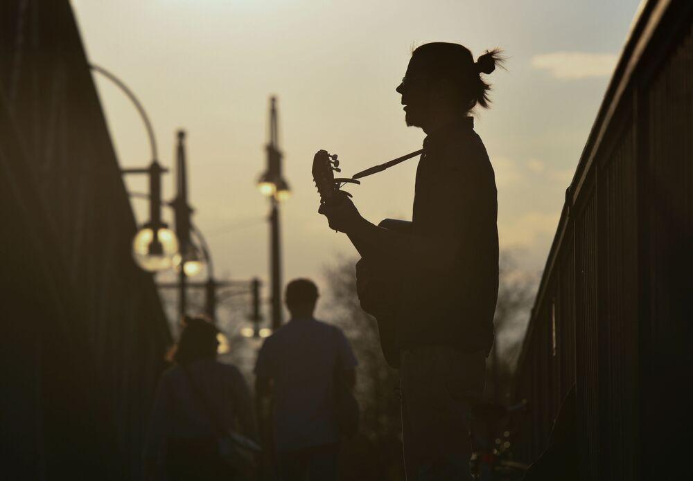 Un uomo suona una chitarra su un ponte al tramonto a Berlino, Germania, il 12 aprile 2020