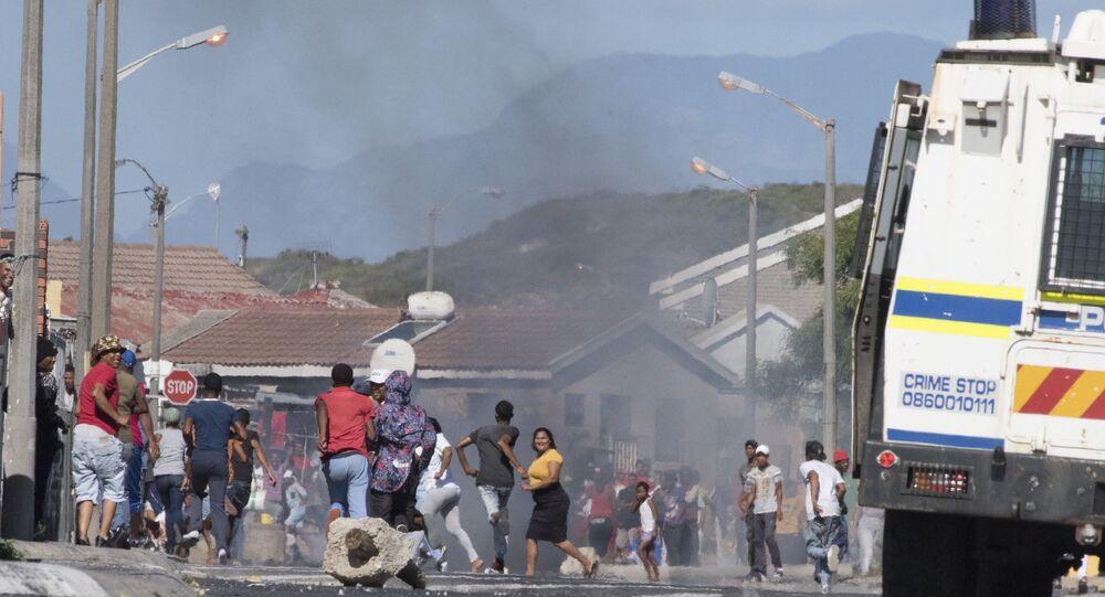 La gente lancia pietre contro un veicolo blindato dei servizi di polizia sudafricano durante gli scontri con i residenti di Tafelsig, un sobborgo povero di Città del Capo.