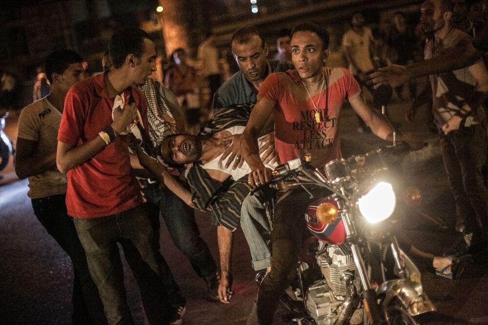 Feriti al Cairo vengono portati via in moto.