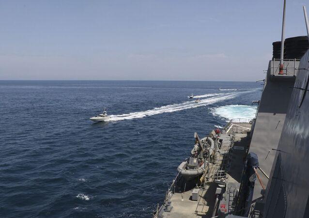 Una motovedetta della Guardia Rivoluzionaria naviga in prossimità di una nave militare della Marina USA nel Golfo Persico, nei pressi del Quwait, 15 aprile 2020
