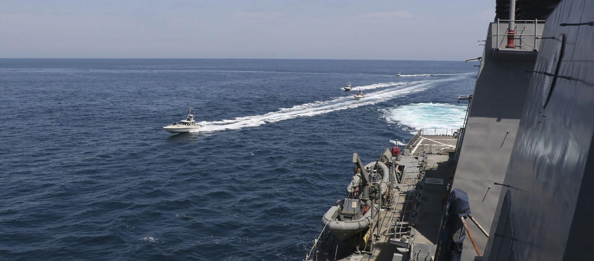 Una motovedetta della Guardia Rivoluzionaria naviga in prossimità di una nave militare della Marina USA nel Golfo Persico, nei pressi del Quwait, 15 aprile 2020 - Sputnik Italia, 1920, 28.04.2021