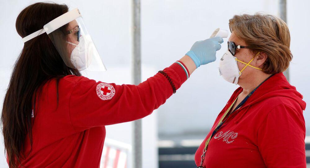 Un volontario della Croce Rossa controlla la temperatura di una cliente di un mercato a Cisterino