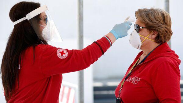 Un volontario della Croce Rossa controlla la temperatura di una cliente di un mercato a Cisterino - Sputnik Italia