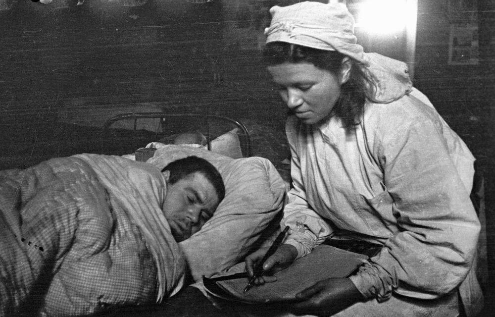 Un'infermiera militare scrive una lettere ai parenti di un soldato ferito.