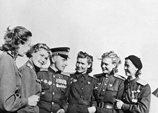 Due volte l'Eroe dell'Unione Sovietica, il comandante della squadriglia del reggimento di caccia, Leonid Beda immortalato tra un gruppo di pilote dei bombardieri. - Sputnik Italia