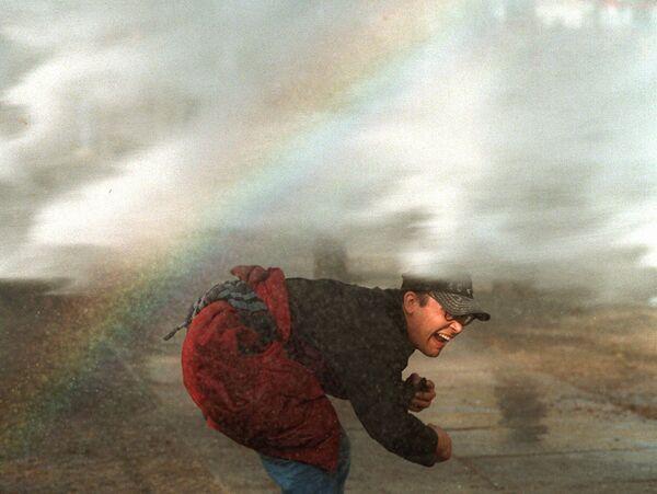 Un manifestante si inchina per evitare un cannone ad acqua della polizia durante gli scontri a Berlino, il 1° maggio 1996. Lavoratori da tutta la Germania sono scesi in piazza per protestare contro i piani del governo di diminuire l'indennità di malattia. - Sputnik Italia
