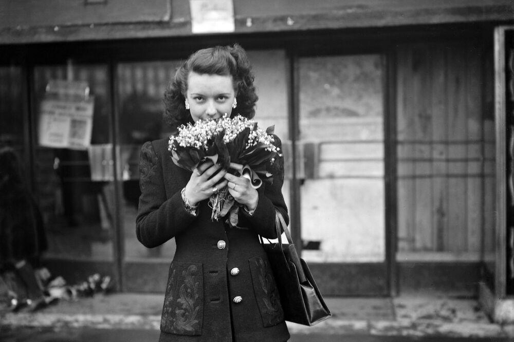 Una ragazza con un mazzo di mughetti in mano il 1° maggio 1945 a Parigi.