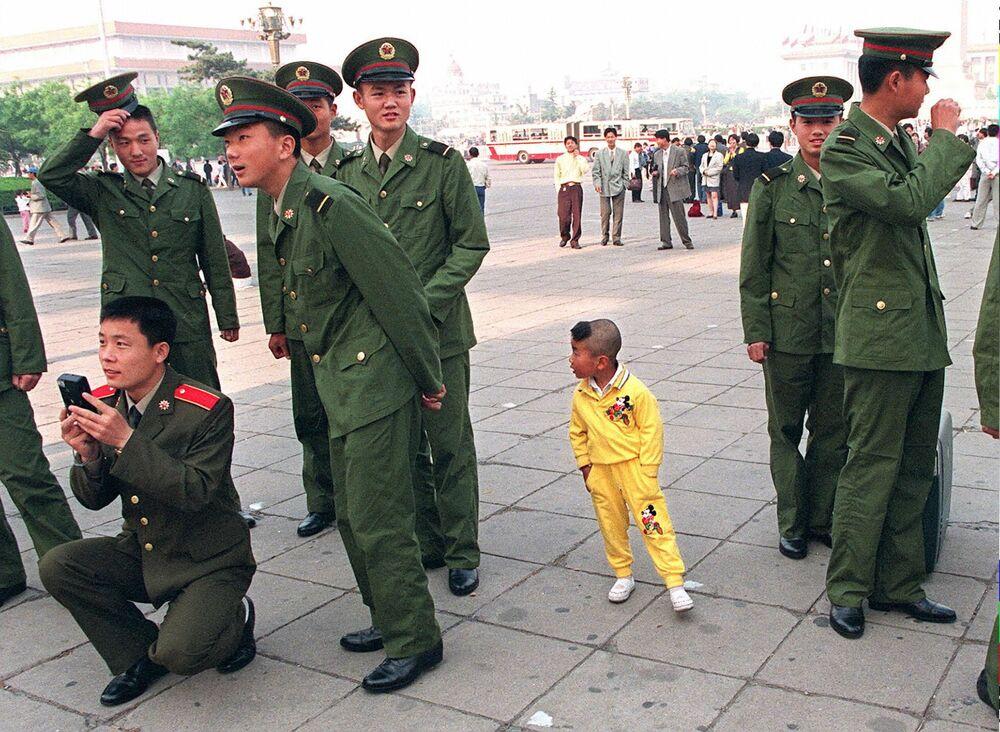 Un bambino visto tra soldati cinesi alla festa del primo maggio a Pechino, 1997.
