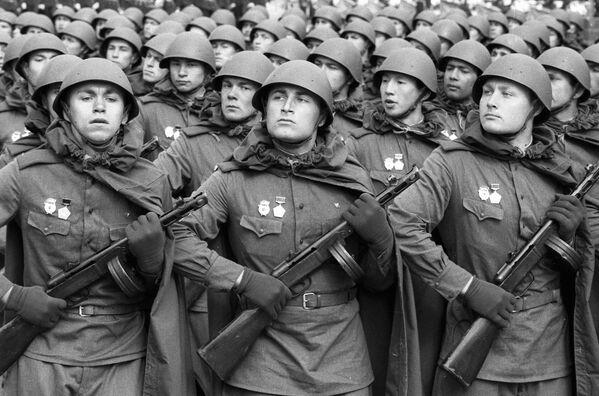 I soldati sovietici vestiti in divisa dell'epoca della Seconda Guerra Mondiale alla parata sulla Piazza Rossa a Mosca per il 40esimo anniversario della Vittoria. - Sputnik Italia