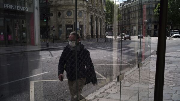 Un uomo indossa una maschera per proteggersi dalla diffusione del nuovo coronavirus mentre cammina in una strada di Parigi - Sputnik Italia