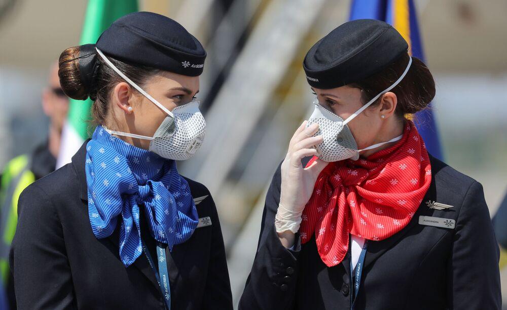 Le assistenti di volo che indossano mascherine protettive accanto a un aereo a Belgrado, Serbia, il 25 aprile 2020