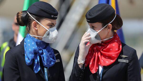 Le assistenti di volo che indossano mascherine protettive accanto a un aereo a Belgrado, Serbia, il 25 aprile 2020 - Sputnik Italia