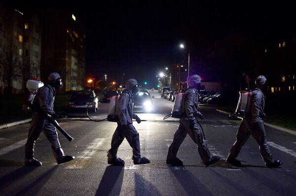 I militari bielorussi che indossano equipaggiamento protettivo attraversano una strada dopo aver disinfettato un ospedale nella città di Zaslauye, fuori Minsk, il 29 aprile 2020 - Sputnik Italia