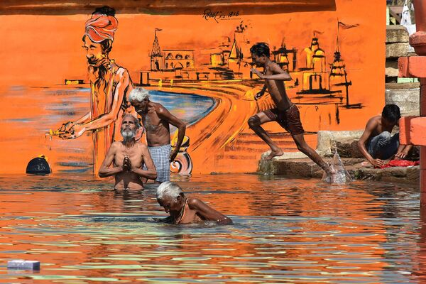 I devoti indù fanno il bagno in occasione di Akshaya Tritiya, un festival annuale di primavera, sul fiume Narmada a Jabalpur, il 26 aprile 2020 - Sputnik Italia