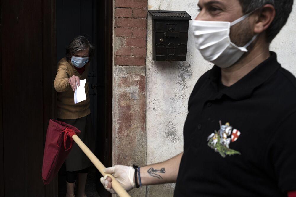 Una donna dà soldi a un membro della fattoria di San Giorgio dopo che le è stato dato il pane durante una distribuzione tradizionale di pane per la festa di San Giorgio a Caresana, Italia, il 26 aprile 2020