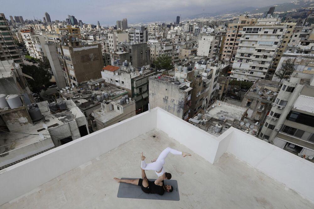 L'istruttore di yoga libanese Rabih el-Medawar, 29 anni, pratica Acroyoga con sua moglie ucraina, collega istruttrice di yoga e coreografa professionista, Alona Aleksandrova, 24 anni, sul tetto del loro condominio nel quartiere Ain El-Remmaneh di Beirut, il 27 aprile 2020