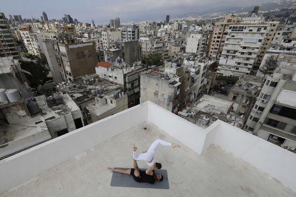 L'istruttore di yoga libanese Rabih el-Medawar, 29 anni, pratica Acroyoga con sua moglie ucraina, collega istruttrice di yoga e coreografa professionista, Alona Aleksandrova, 24 anni, sul tetto del loro condominio nel quartiere Ain El-Remmaneh di Beirut, il 27 aprile 2020 - Sputnik Italia