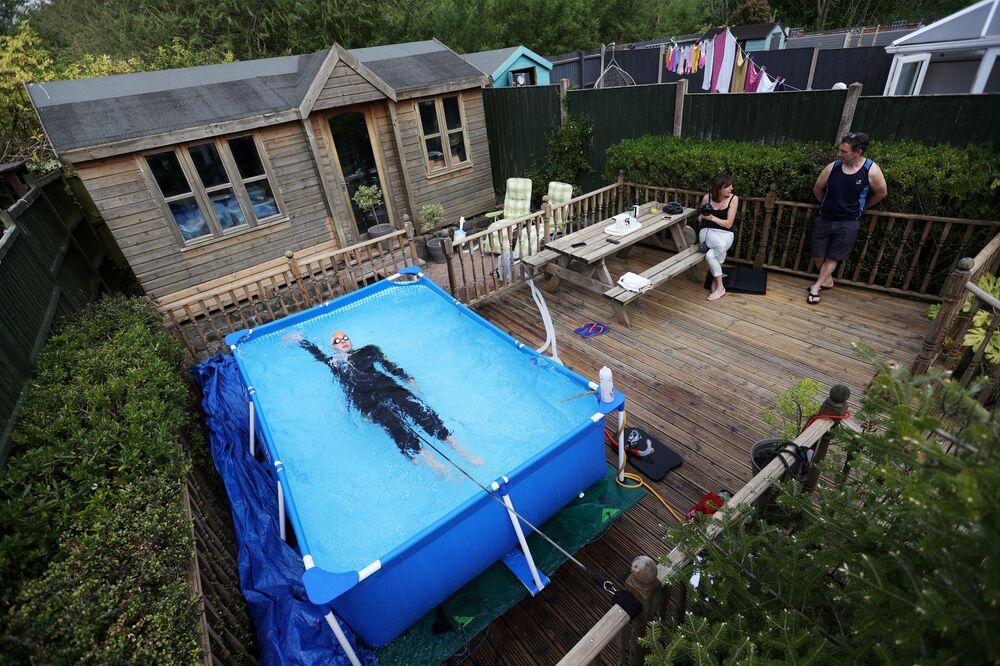 Il triatleta Lloyd Bebbington si allena in una piscina nel suo giardino di casa a Newcastle-under-Lyme, Gran Bretagna, il 26 aprile 2020
