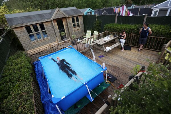 Il triatleta Lloyd Bebbington si allena in una piscina nel suo giardino di casa a Newcastle-under-Lyme, Gran Bretagna, il 26 aprile 2020 - Sputnik Italia