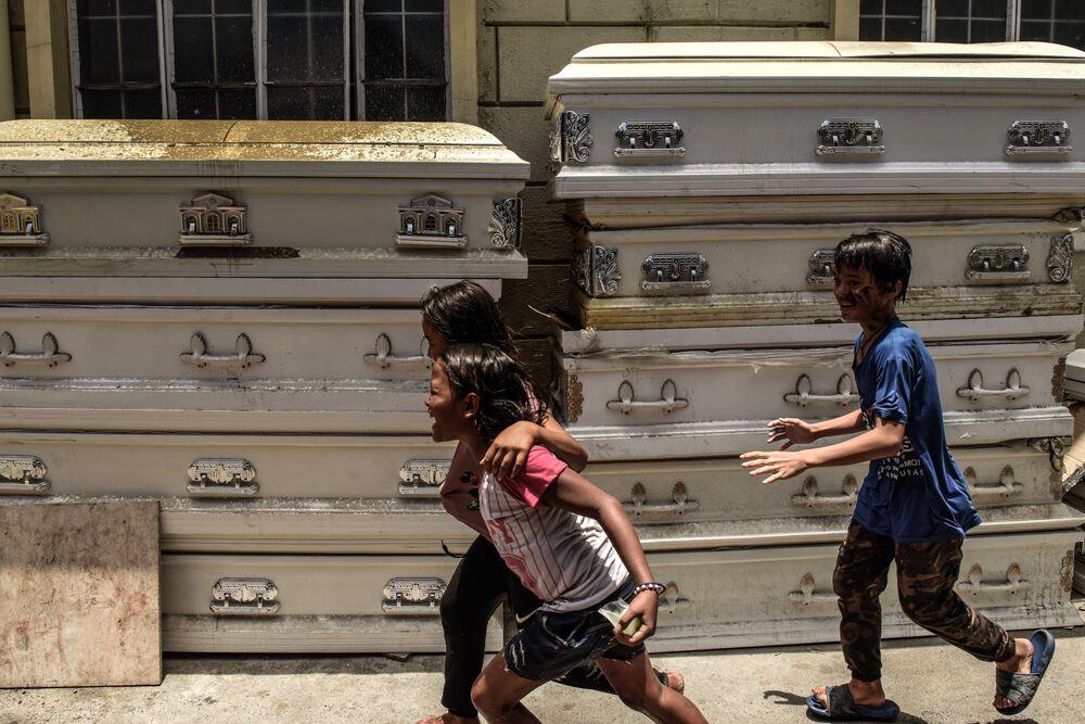 Bambini giocano davanti ad un crematorio di Manila